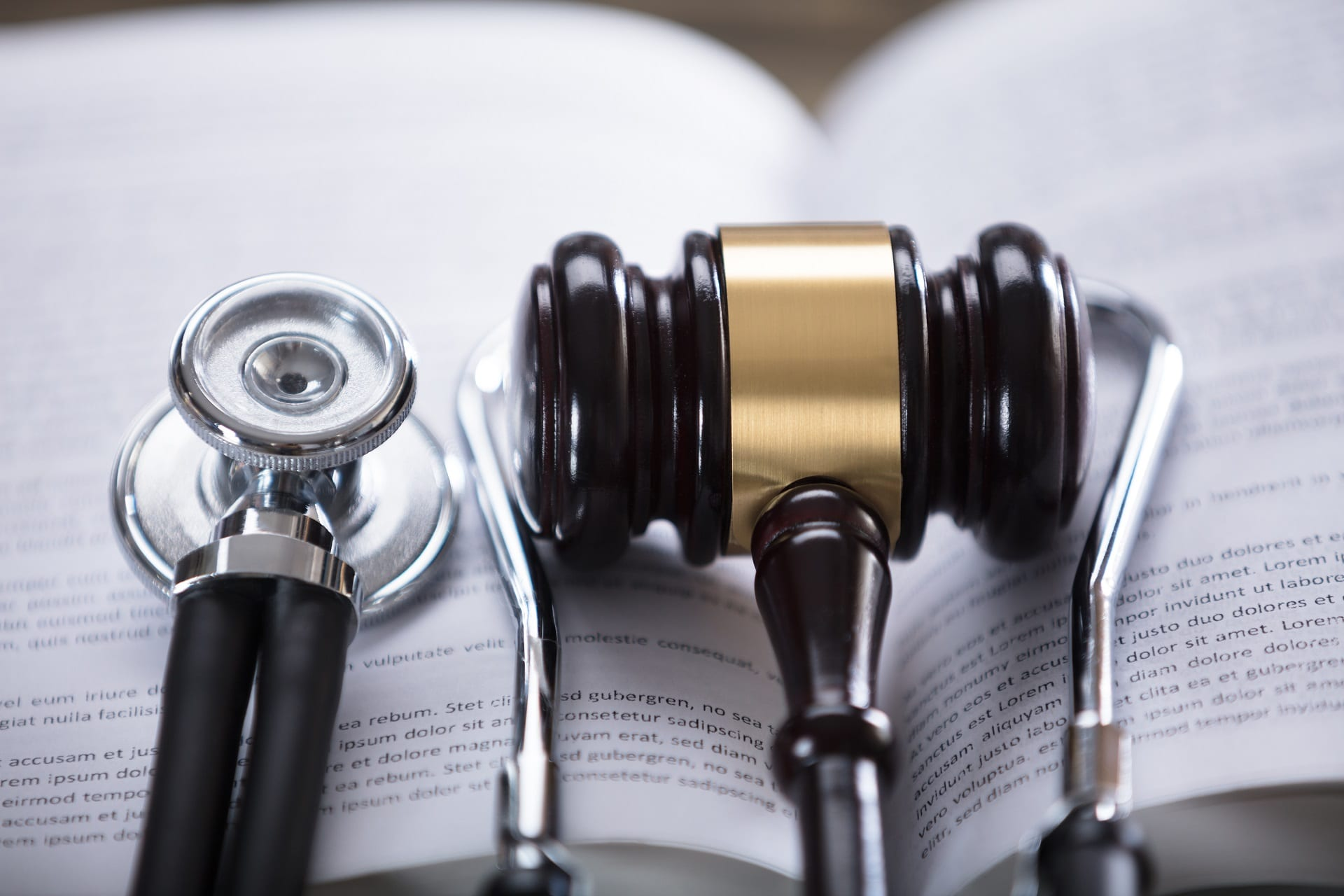 Close-up Of Stethoscope And Gavel laying atop an open book