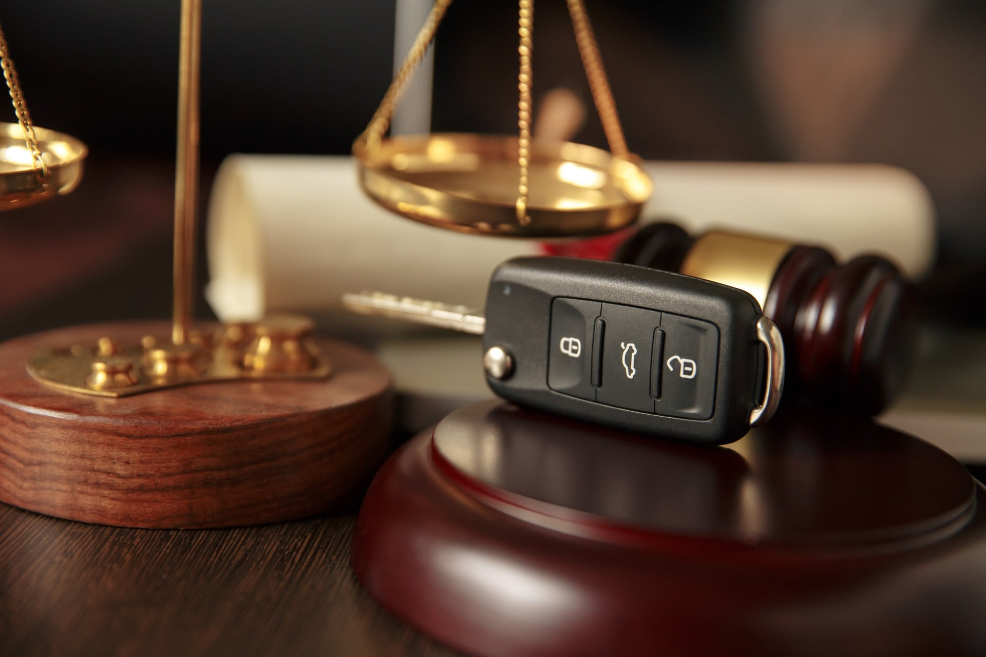 Car keys sitting atop a wooden referee, next to a gavel and the scales of justice