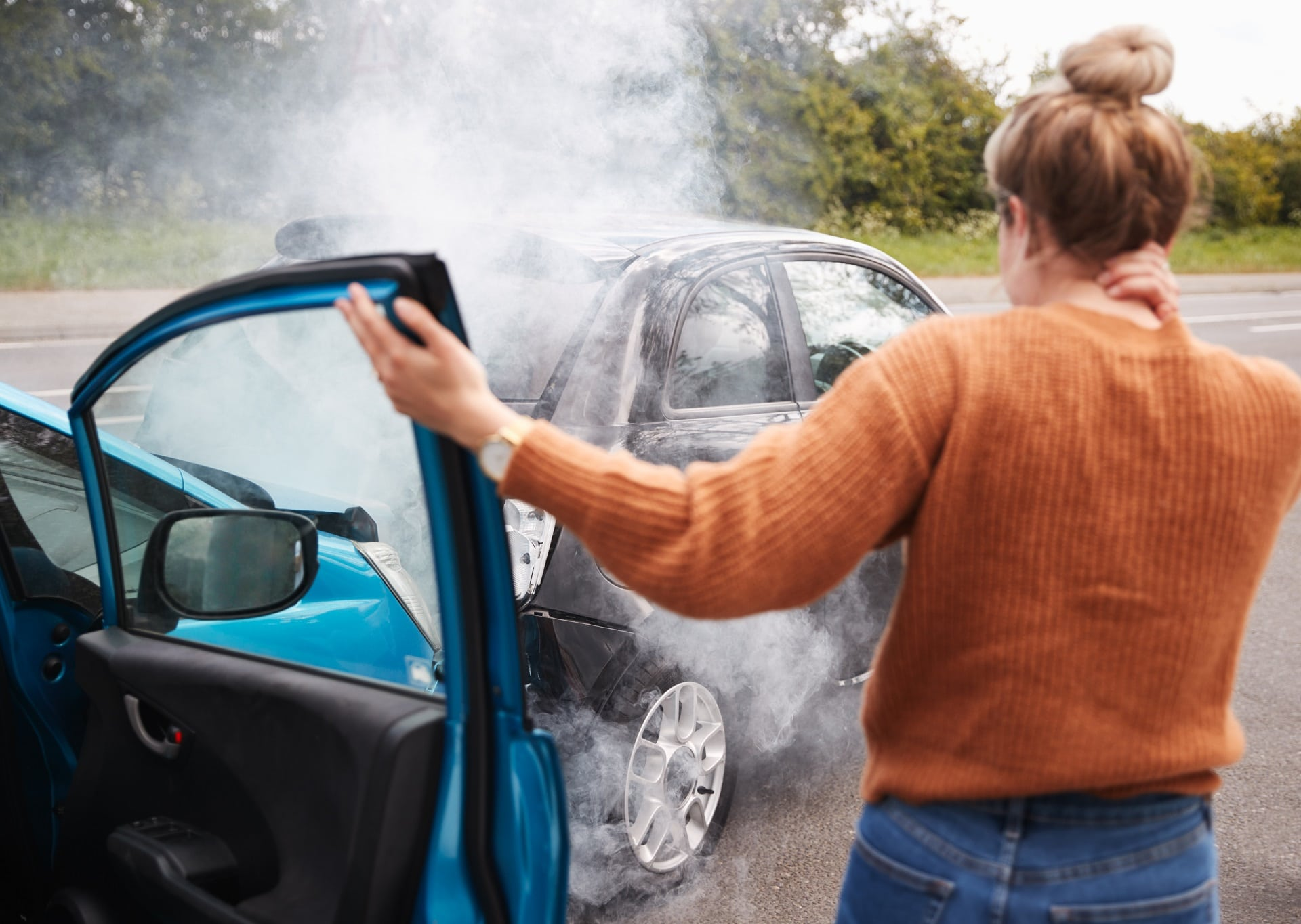 Smoking rear-ended car accident with woman at one car door, holding her neck