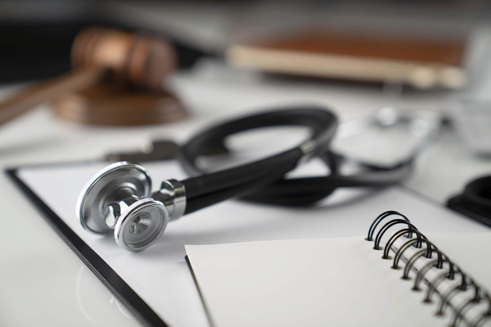 Stethoscope atop papers with blurred out gavel and block in background