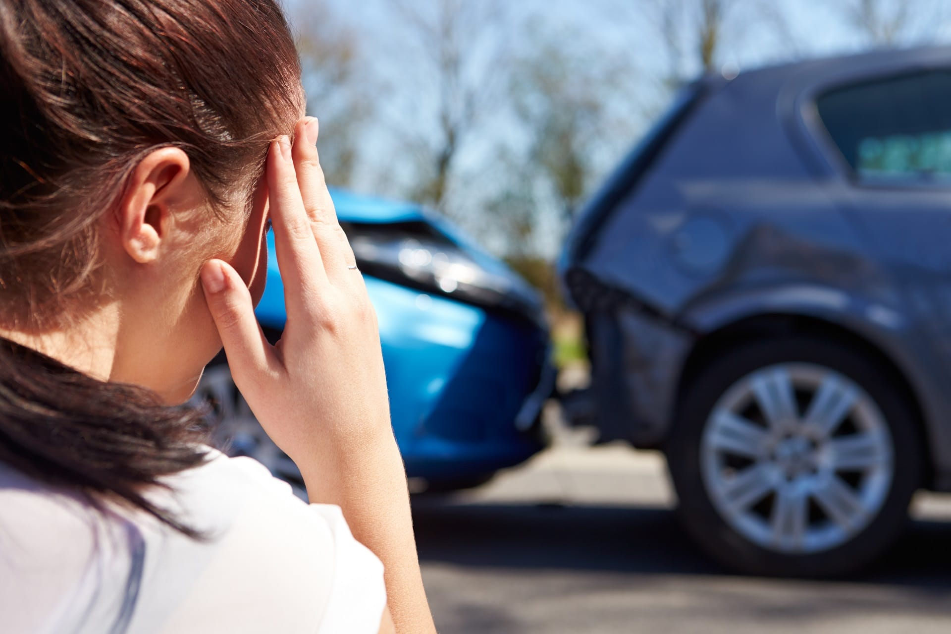 Woman with a hand to her head looking towards a rear-end car accident
