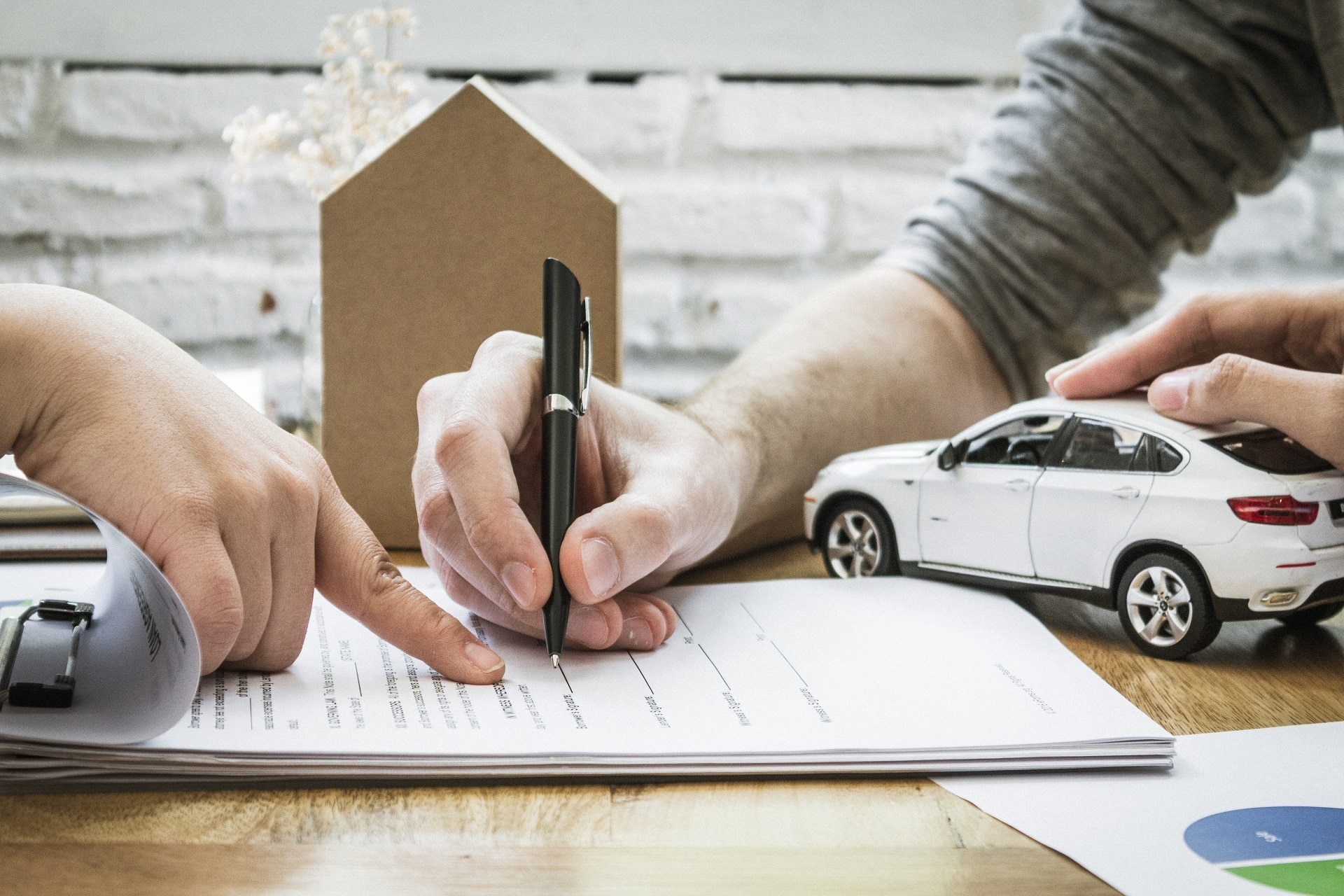 Man signing document with a woman's hand on a toy model car