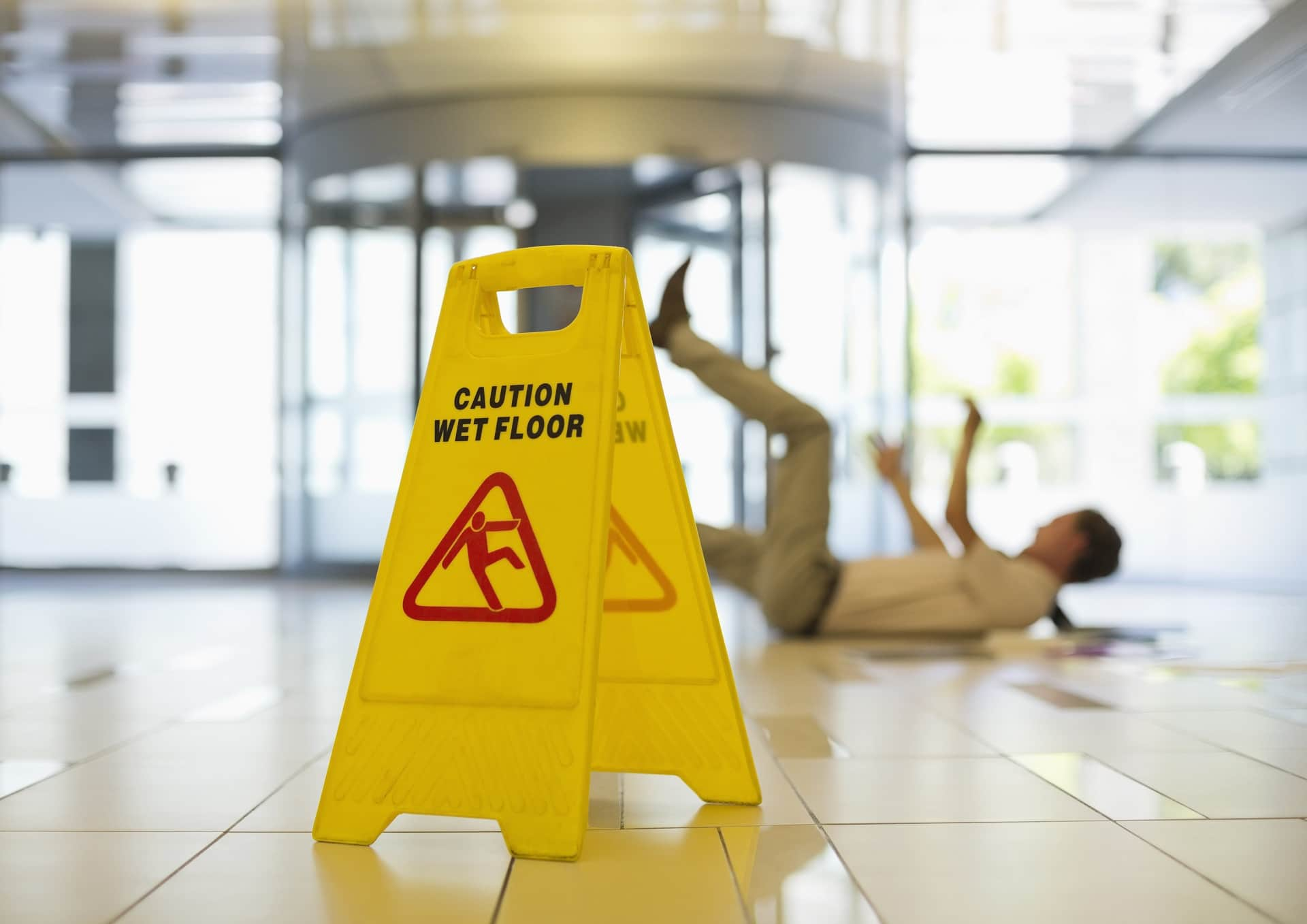 Yellow caution wet floor sign with blurred out fallen man in background