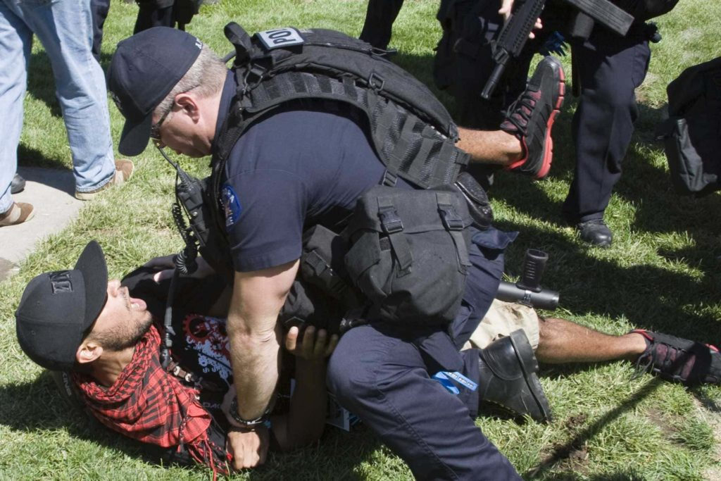 angry protester tackled by police officer