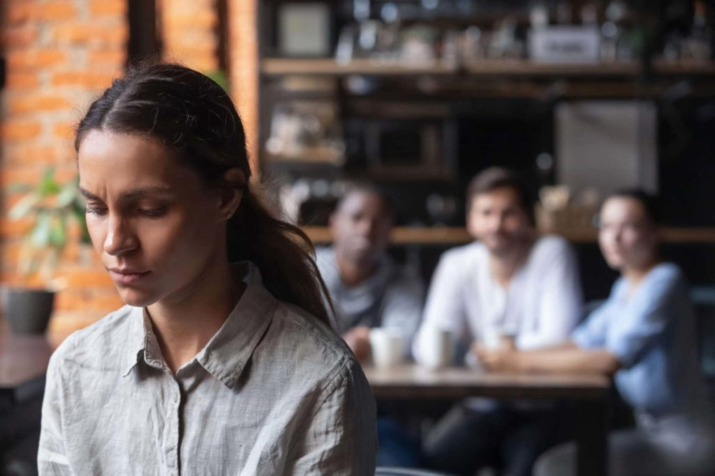 distressed mixed race woman in foreground with mocking coworkers looking on