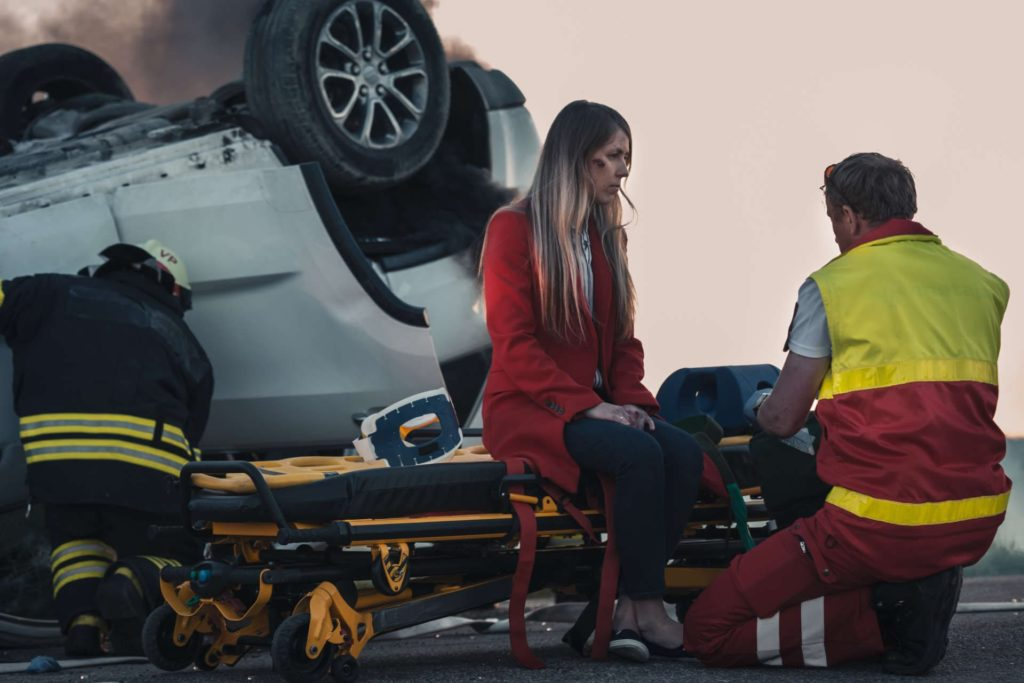 injured woman attended to by medic next to flipped car