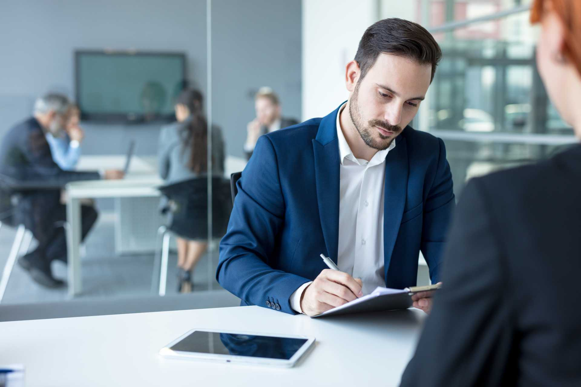 Businessman completing paperwork with meeting taking place behind him