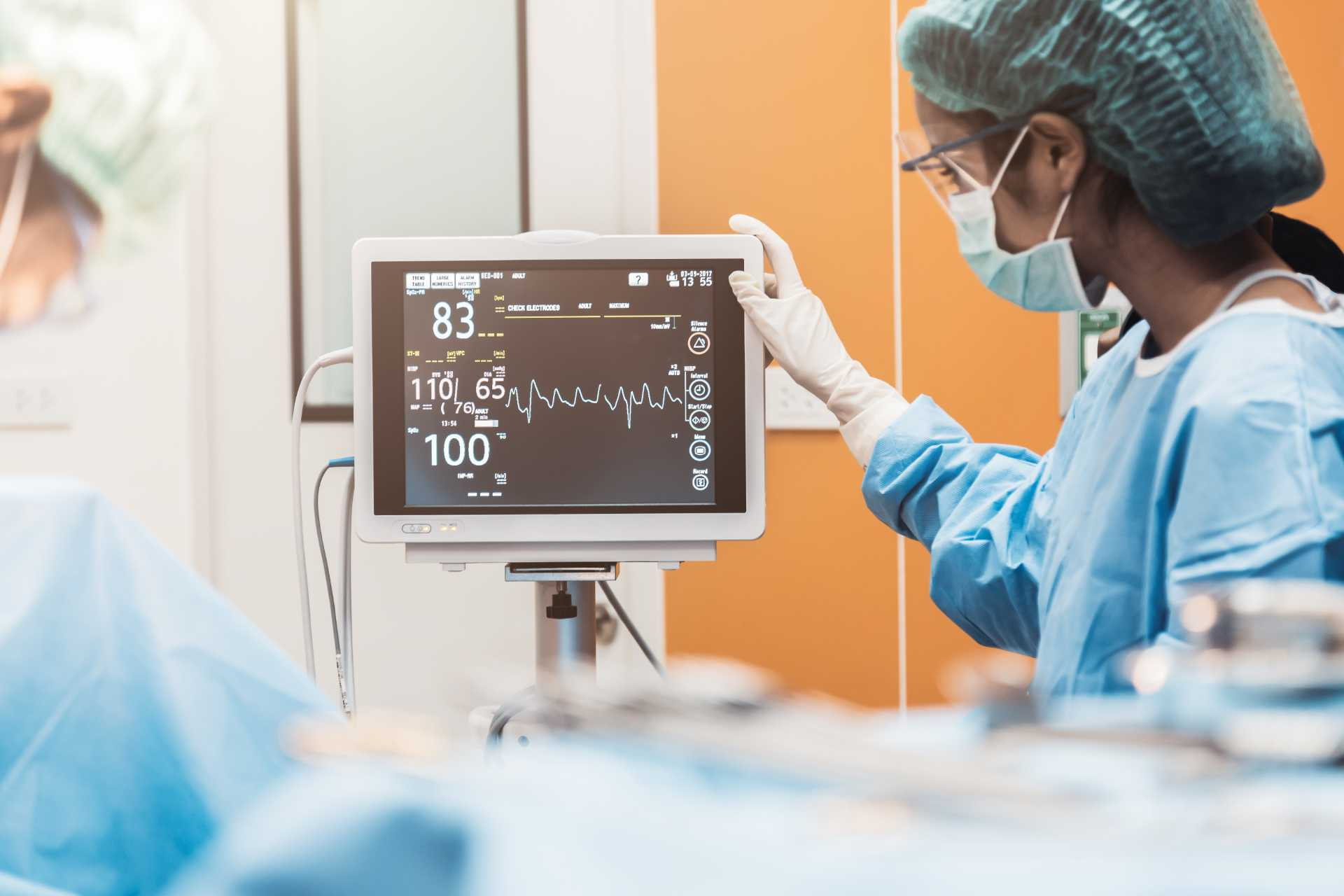 nurse checking vital screen in surgical room