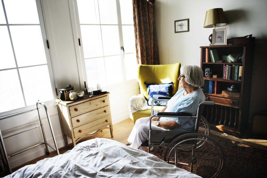 Older woman in wheelchair looking out sunlit window