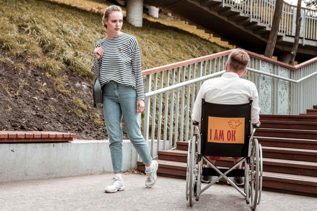 woman frowns upon wheelchair man in front of stairs