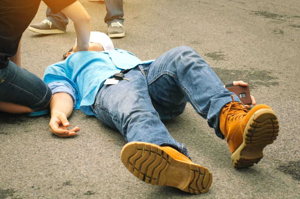 worker injured on pavement attended to by coworker